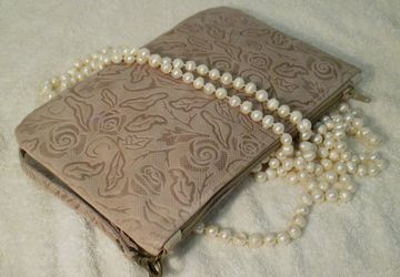 A beige leather clutch with floral design