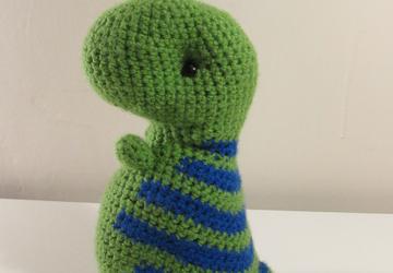 Green dinosaur with blue stripes