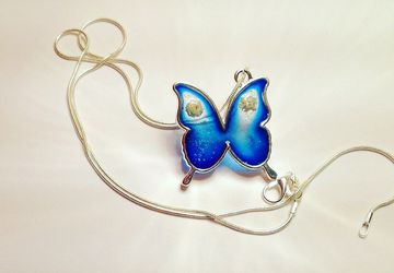 Silver necklace with pendant. Blu resin butterfly and flowers