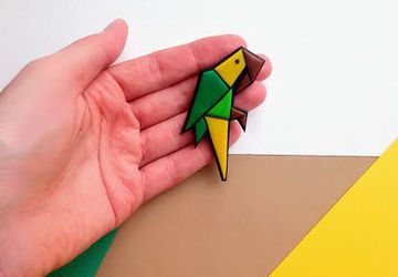Origami style parrot brooch made from polymer clay in green and yellow tones