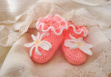 Knitted pink baby-shoes with a flower